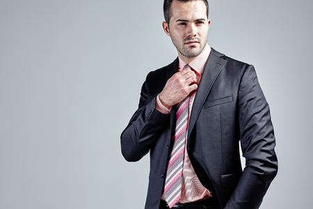 Portrait of young fashionable businessman fixing his tie isolated over grey Stock Photo