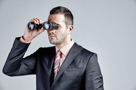 Handsome businessman using binocular isolated over grey Stock Photo