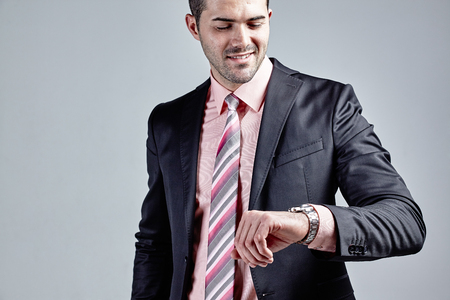 Close up of businessman checking his wrist watch and smiling isolated over grey