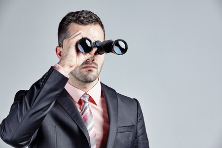 man looking at sky: Businessman with binocular isolated over grey Stock Photo