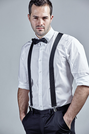 Man with suspenders and bow tie isolated over grey Stock Photo