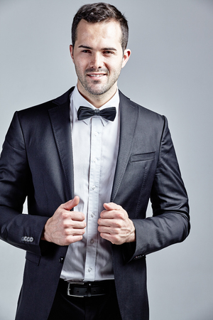 Portrait of young and handsome man wearing black suit and bow tie isolated over grey Stock Photo