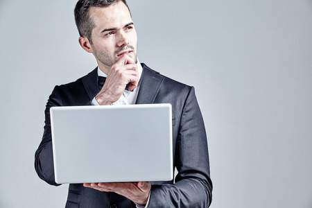 Businessman holding his finger at chin while working on a laptop isolated over grey Stock Photo