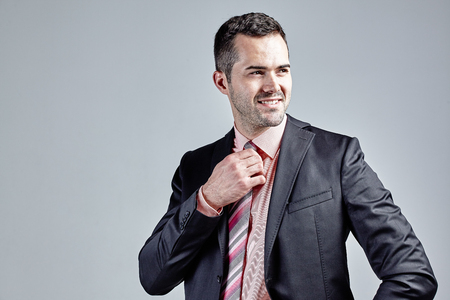 Young smiling businessman arranging his tie isolated over grey Stock Photo