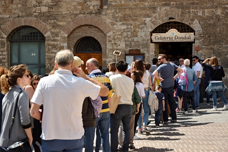 SAN GIMIGNANO, ITALIA - ABRIL DE 2017 - Cola larga para el mejor helado del mundo de Gelateria Dondoli en San Gimignano, Toscana, Italia