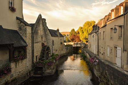 Old water canal with water wheel in Bayeux, Normandy, France