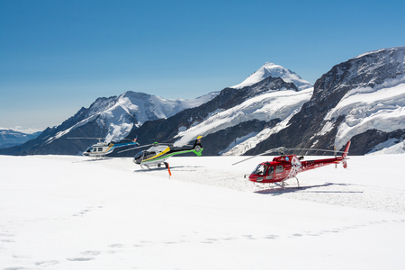 JUNGFRAUJOCH, SWITZERLAND - AUGUST, 2015 - Three sightseeing helicopters standing on top of Aletsch glacier near Jungfraujoch, Switzerland Editorial