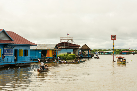 TONLE SAP LAKE, CAMBODIA - OCTOBER 20, 2014: Inhabitants of floating village near Siem Reap on Tonle Sap lake in Cambodia performing their daily routine on cloudy day