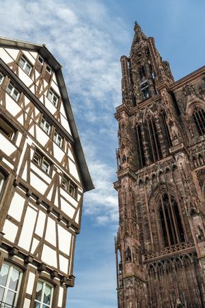 Contrast between Strasbourg Cathedral and old medieval house in Strasbourg, France Standard-Bild - 100430477