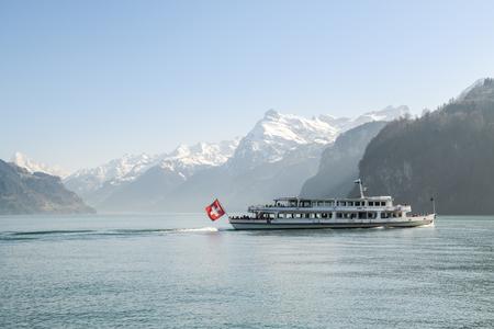 BRUNNEN, SWITZERLAND - APRIL 7, 2018: Cruise ship with tourists on Lake Lucerne near Brunnen in Switzerland during spring 2018