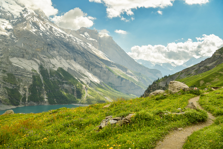 Winding walking trail high above the Oeschinensee lake with picturesque panorama of Swiss Alps
