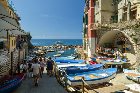 RIOMAGGIORE, ITALY - JUNE 29, 2018: Tourists walking through tiny harbor in city of Riomaggiore in Cinque Terre, Italy in June 2018
