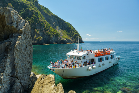 RIOMAGGIORE, ITALY - JUNE 29, 2018: Overcrowded regular ferry boat near Riomaggiore in Cinque Terre, Italy in June 2018. Boat is popular tourist attraction as it provides different perspective on Cinque Terre cities