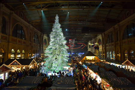 Zurich, Switzerland - December 15, 2018: People visiting traditional christmas market on Zurich main train station in Switzerland. Market is dominated by tall christmas tree decorated by Swarovski. Editorial