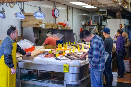 New York City, USA - October 5, 2018: Potentional buyer looking at fish in small shop with sea products in Chinatown in Manhattan, New York City during October 2018 Editöryel