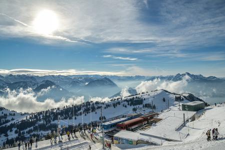 igi Kulm, Switzerland - January 4, 2019: Tourists enjoying their views on Swiss Alps near train station on top of Mount Rigi, Switzerland during sunny winter day