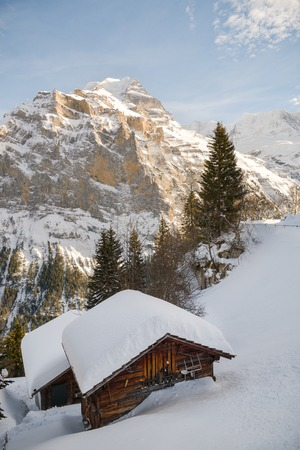 Small wooden hut covered by snow in front of majestic Jungfrau peak in Bernese Alps, Switzerland