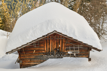 Wooden hut covered by snow in Swiss Alps