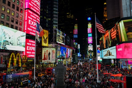 New York City, United States - October 5, 2018: Tourists enjoying their time on Times Square in New York City after sunset during October 2018