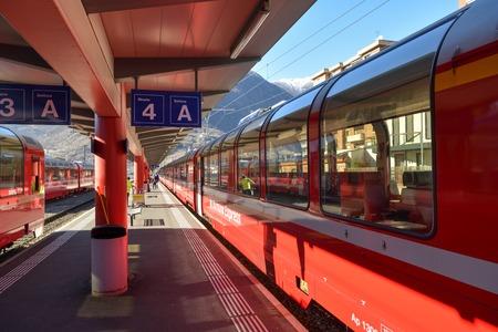 Tirano, Italy - February 16, 2019: Red Bernina Express train on train station in Tirano, Italy during February 2019