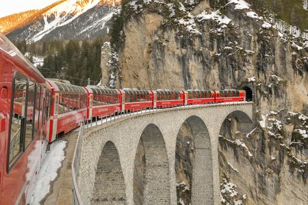 Filisur, Suisse - 16 février 2019 : Train Bernina Express rouge typique à cheval sur le célèbre viaduc de Landwasser près de la ville de Filisur en Suisse pendant l'hiver 2019
