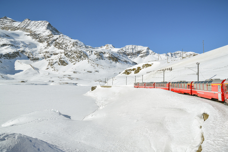 Bernina Pass, Switzerland - February 16, 2019: Typical red Bernina Express train riding through the Bernina pass, highest point of the route in Swiss Alps during February 2018 Редакционное