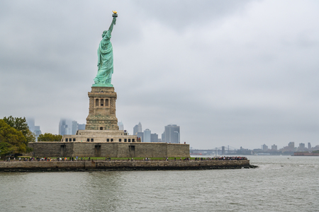 New York City, USA - October 8, 2018: Crowd of tourists visiting Statue of Liberty on Liberty Island, New York City, USA during cloudy October day 2018