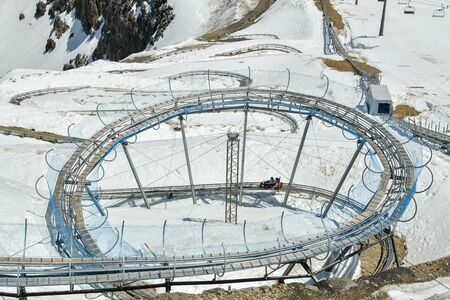Glacier 3000, Switzerland - June 8, 2019: People riding on the toboggan on top station on Glacier 3000  in canton of Vaud, Switzerland during June 2019