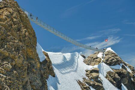 Glacier 3000, Suiza - 8 de junio de 2019: Gente caminando sobre el puente colgante en el pico Scex Rouge en la cima del Glaciar 3000 durante el día soleado en junio de 2019