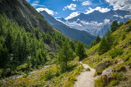 Hiking trail to Saas-Almagell village in Swiss Alps with incredible views on majestic peaks in background Archivio Fotografico