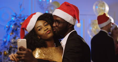 Portrait of young happy African American couple in santa clause hats taking selfies on a smart phone at the New Year or Christmas party. Dancing people background. Indoor Stock Photo - 90881741
