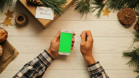 Top view. Male hands tapping, scrolling and zooming on the white smart phone. The white desk with Christmas stuff. Green screen, chroma key.
