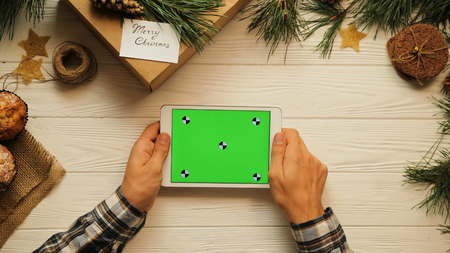 View from above. Male hands tapping, scrolling and zooming on tablet device horizontally. The Christmas decorated white desk. Green screen, chroma key. Tracking motion.