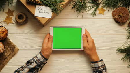 Top view. Male hands tapping, scrolling and zooming on tablet divice horizontally on the white desk. Christmas atmosphere. Green screen, chroma key. Stok Fotoğraf