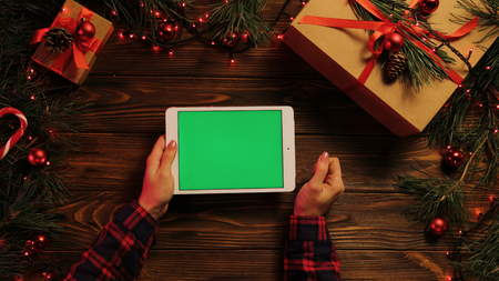 Top view of woman hands tapping, scrolling and zooming on tablet divice horizontally. The Christmas decorated brown desk with Christmas lights. Green screen, chroma key Stok Fotoğraf