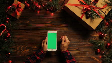 Top view. Woman tapping, scrolling and zooming on the mobile phone vertically. The decorated wooden desk with garlands. Christmas stuff. Green screen, chroma key.