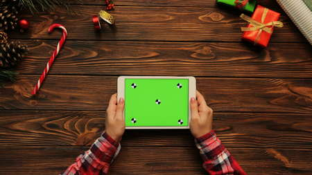 View from above on woman holding her white tablet on the Christmas decotated wooden table, Green screen, chroma key, tracing motion