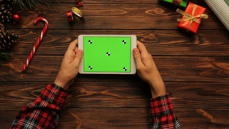 View from above on man holding his white tablet on the Christmas decotated wooden table, Green screen, chroma key, tracing motion