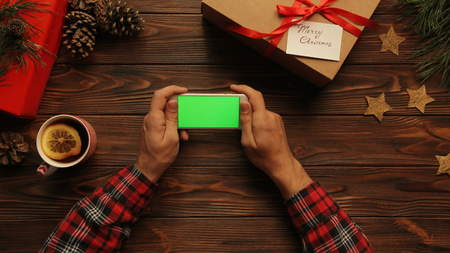 View from above on man holding his white smart phone on the Christmas decotated wooden table, Green screen, chroma key, tracing motion
