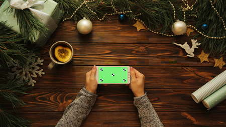 Top view of Woman hands tapping, scrolling and zooming on white mobile horizontal phone on the Christmas decorated wooden desk, green screen, chroma key, tracking motion