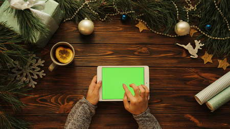 Woman hands tapping, scrolling and zooming on white tablet horizontally on the Christmas decorated wooden desk, green screen, chroma key, top view Stok Fotoğraf