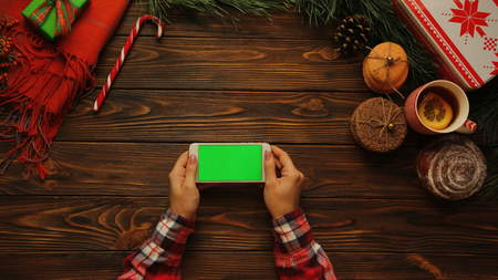 Female hands tapping, scrolling and zooming on white mobile phone horizontally. The Christmas decorated wooden desk. Green screen, chroma key, top view