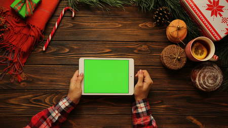 Female hands tapping, scrolling and zooming on white tablet device horizontally on the brown wooden desk. The Christmas decorations. Green screen, chroma key. View from above.