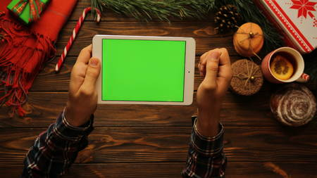 Top view of male hands tapping, scrolling and zooming on white tablet device horizontally on the brown wooden desk. The Christmas mood. Green screen, chroma key.