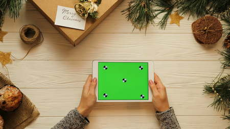 View from above. Female hands tapping, scrolling and zooming on tablet divice horizontally. The Christmas decorated white desk. Green screen, chroma key. Tracking motion. Stok Fotoğraf - 90881619