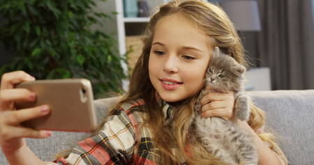A little blonde cute girl making funny selfies with a kitty-cat on the smart phone while sitting on the couch. Inside Banco de Imagens