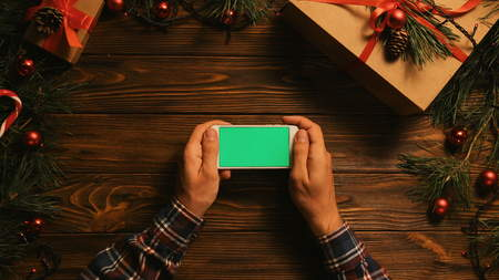 Male hands holding white smartphone with green screen on the wooden table with christmas decoration. Chroma key. Horizontal position. View from above