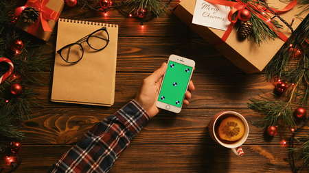 Chrismas flat lay with garlands, gift box, notebook and smartphone with green screen. Man using phone and drinking tea. Chroma key. Tracking motion
