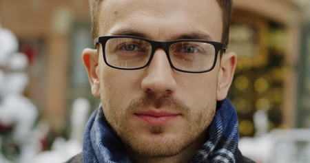 Portrait of the handsome caucasian man in glasses and scarf smiling sincerely to the camera on the winter day in town street. Blurred christmas decorations on the background. close up. Outdoors Stock Photo