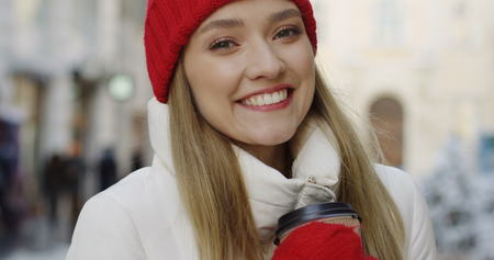 Close up of the charming young woman with blonde hair in red hat and gloves smiling sincerely and holding coffee to go cup on the blurred town background. Winter time. Portrait. Indoors